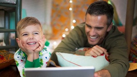 Father and son smiling looking at their laptop device.