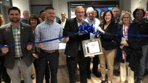 Comcast Beltway region employees in new Xfinity store standing in front of a ribbon